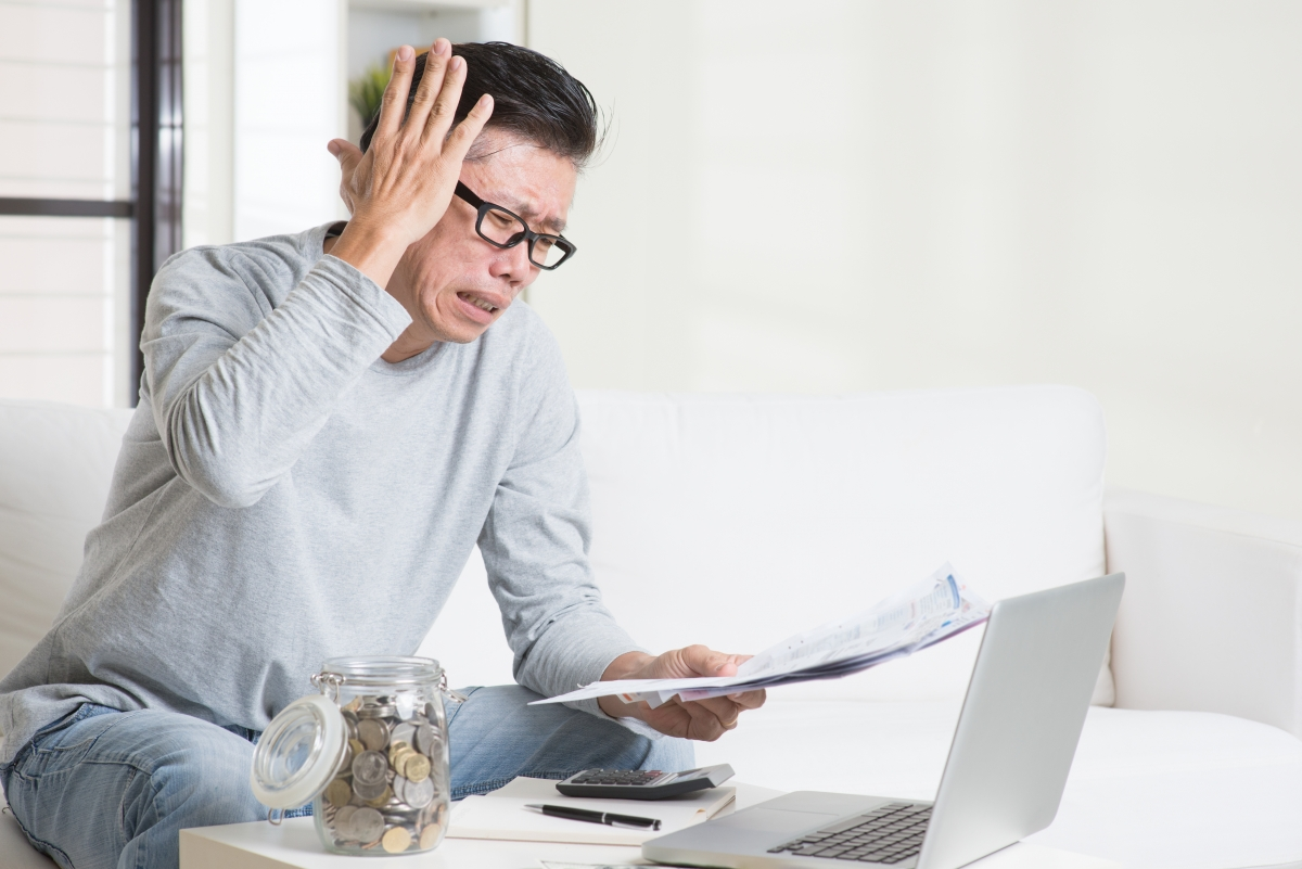 Portrait of 50s mature Asian man having a hard time paying bills