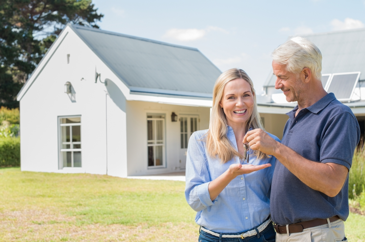 Cheerful senior couple standing outside their new house with key